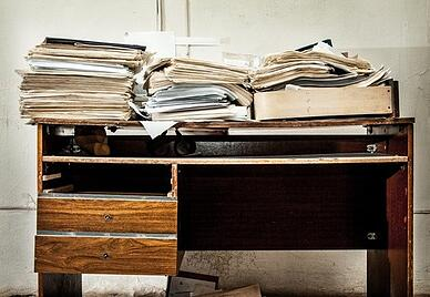 Desk covered with paper documents.