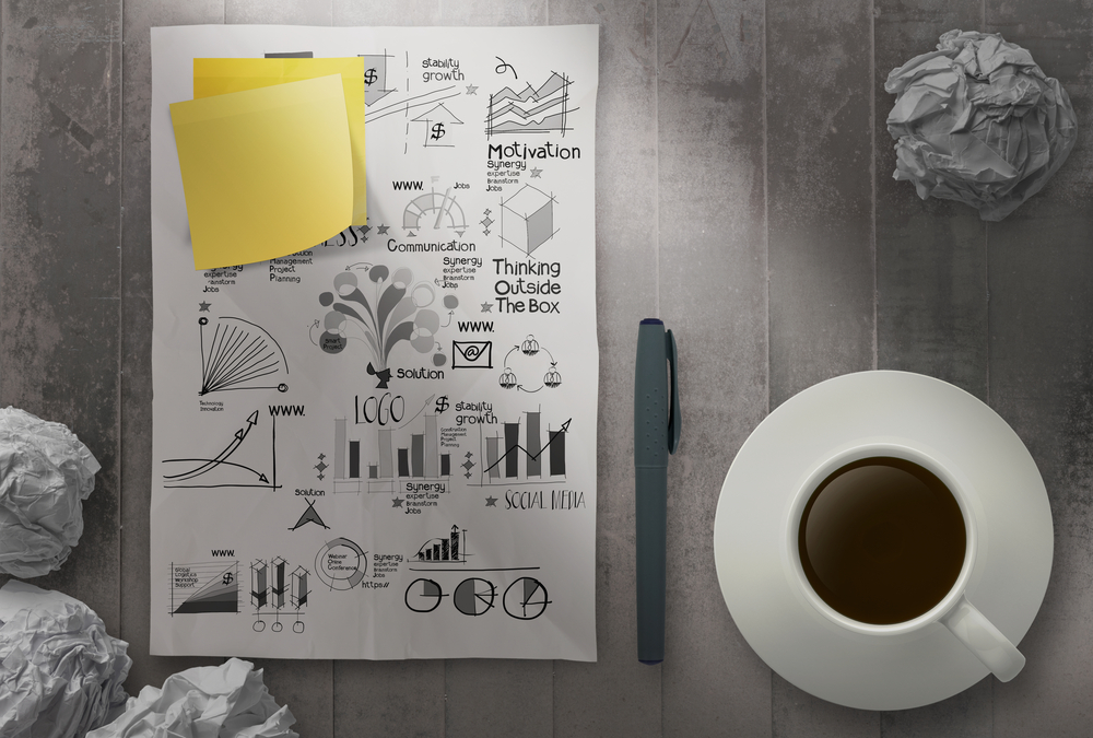 coffee cup with crumpled paper of hand drawn business strategy and blank sticky note background as concept